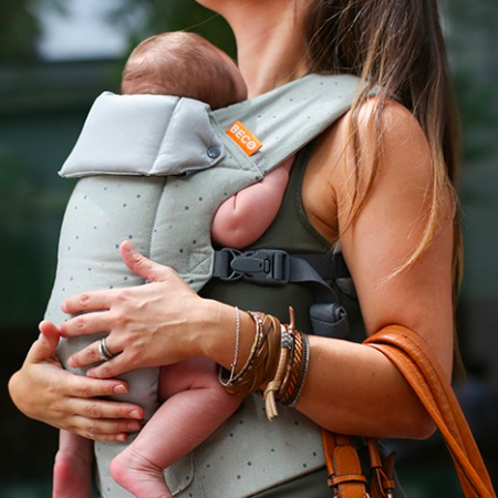 Beco Gemini - model wears smaller baby in carrier, facing in