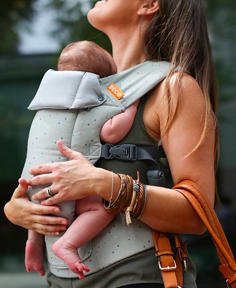 Beco Gemini - model wears smaller baby in carrier, facing in