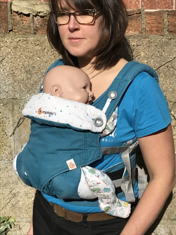 Lucy carrying creepy fake baby in Ergo 360